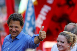 Brazil's Workers Party presidential candidate Fernando Haddad attends a rally next to Senator Gleisi Hoffman in Curitiba