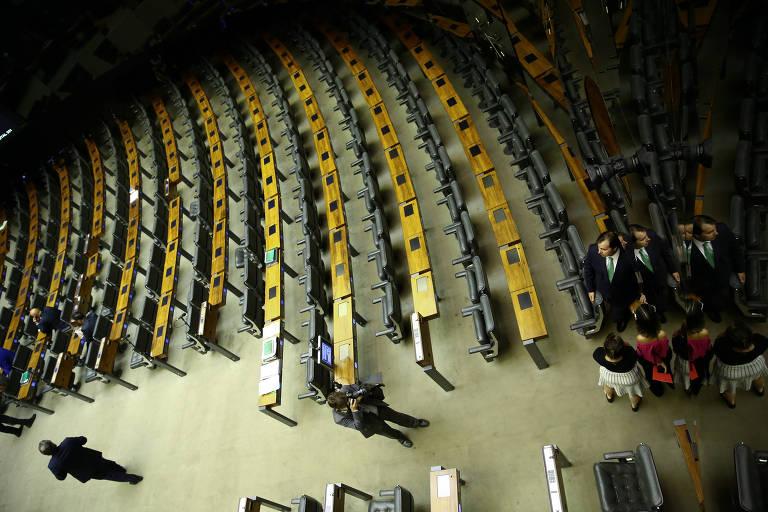 Fileiras de cadeiras vazias vistas de cima no plenário da Câmara, algumas pessoas caminham no corredor