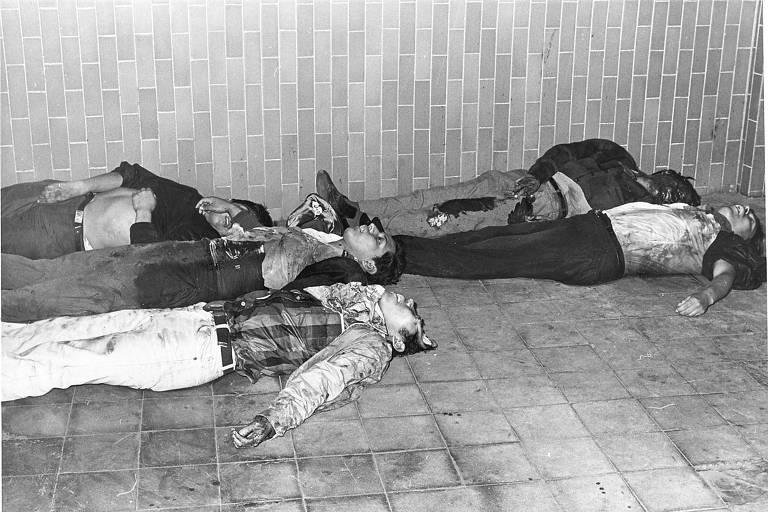 Quatro corpos de homens aparecem em um chão de piso frio: dois enfileirados em cima e outros dois embaixo