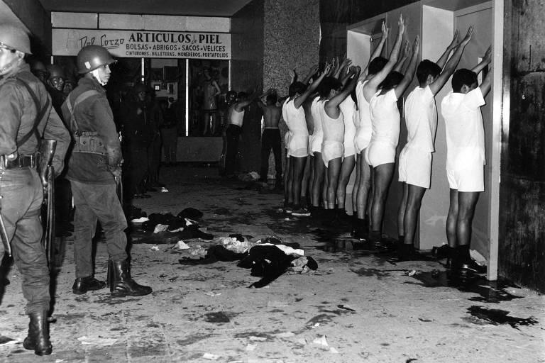 Um grupo de sete homens aparece apenas em roupa de baixo branca com as mãos para cima enquanto soldados os observam