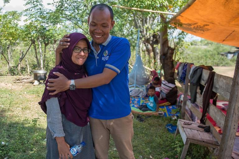 Azwan abraça sua mulher, Dewi Prasasti, em frente à casa da família em Palu, na ilha de Sulawesi