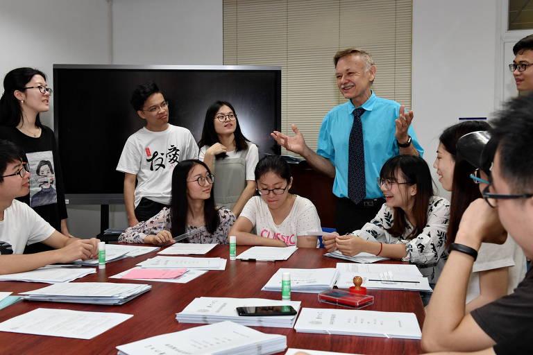 Seis alunos estão sentados a uma mesa de reunião, enquanto outros quatro estão de pé, olhando o professor falar. Na mesa há diferentes pilhas de papel e ao fundo do grupo em pé está uma televisão de tela plana.