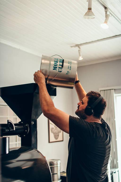 Hugo Rocco, da Moka Clube, e a máquina para torrar o café que ele envia aos seus assinantes