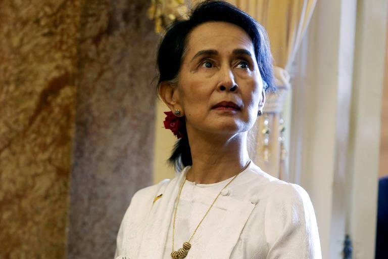 Com feições sérias, Suu Kyi aparece olhando para o lado direito