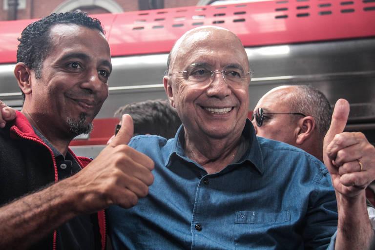 Ao lado de um eleitor, Henrique Meirelles faz sinal de positivo com o polegar da mão esquerda em evento de sua campanha que aconteceu em uma estação da CPTM