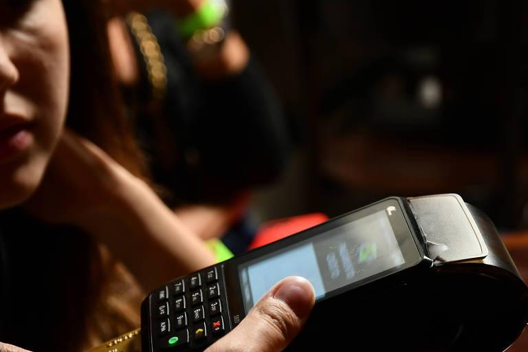 Uma pessoa faz um pagamento via maquininha de cartão de crédito