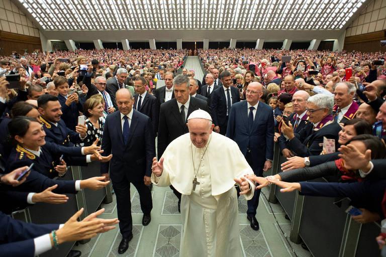 Francisco aparece ao centro, acompanhado por três seguranças. Nas laterais, policiais tentam segurar na mão do pontífice.