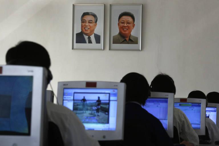 Grupo de estudantes em seis fileiras usa computadores com monitores de tubo. Na parede à frente as fotos dos líderes norte-coreanos.