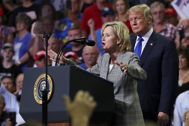 De terno preto, camisa branca e gravata azul, Trump aparece atrás de Hyde-Smith, que discursa em um púlpito preto com o brasão do Presidente dos EUA. Ao fundo, seguidores do Partido Republicano.