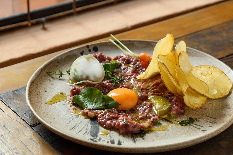 Peito de pato picado, servido com chips de batata e uma gema de ovo servido no Grecco, em Pinheiros