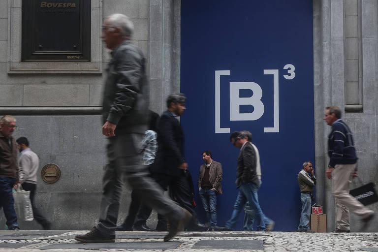 Pessoas caminham em frente à B3, Bolsa de Valores de São Paulo.