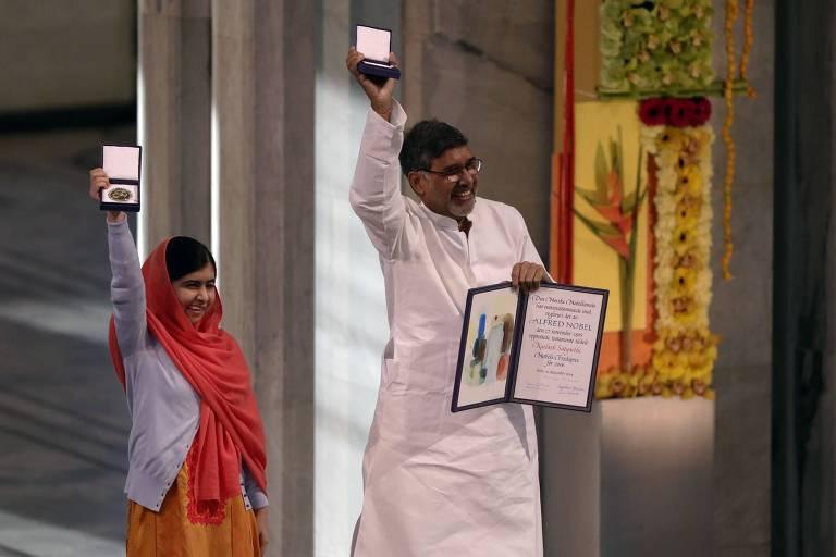 Malala (à esquerda) e Satyarthi levantam suas medalhas do Nobel da Paz. O indiano ainda segura com a mão direita o diploma.