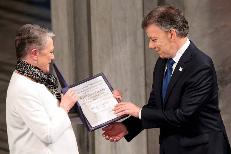 Santos segura o diploma ao lado da membro do Comitê do Nobel Berit Reiss-Andersen