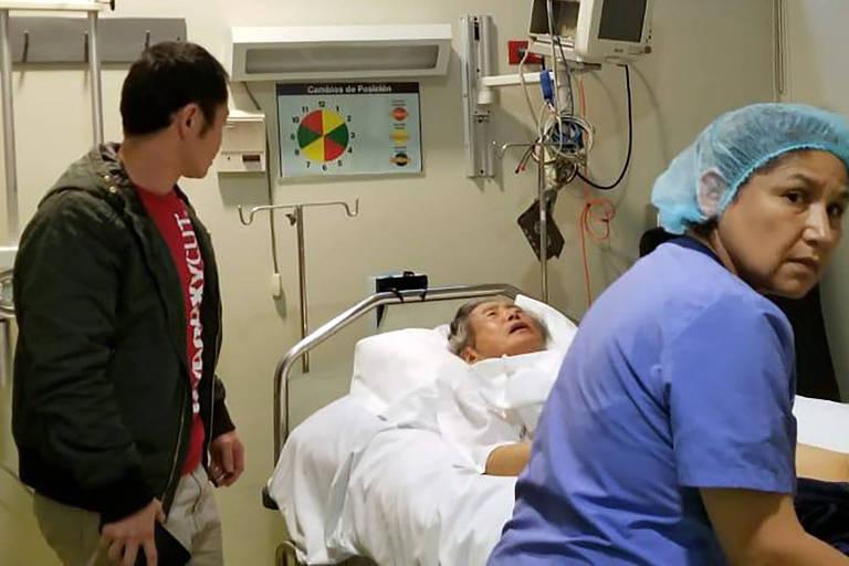 Fujimori está em uma maca, carregada por uma enfermeira. Ao lado dele, uma pessoa de pé o observa.