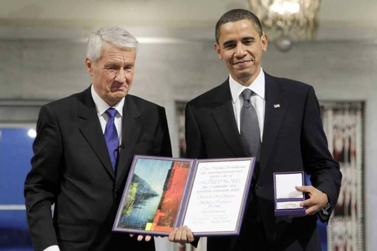 Obama aparece à direita, segurando a medalha com a mão esquerda e o diploma com a direita, enquanto Jagland sai à direita