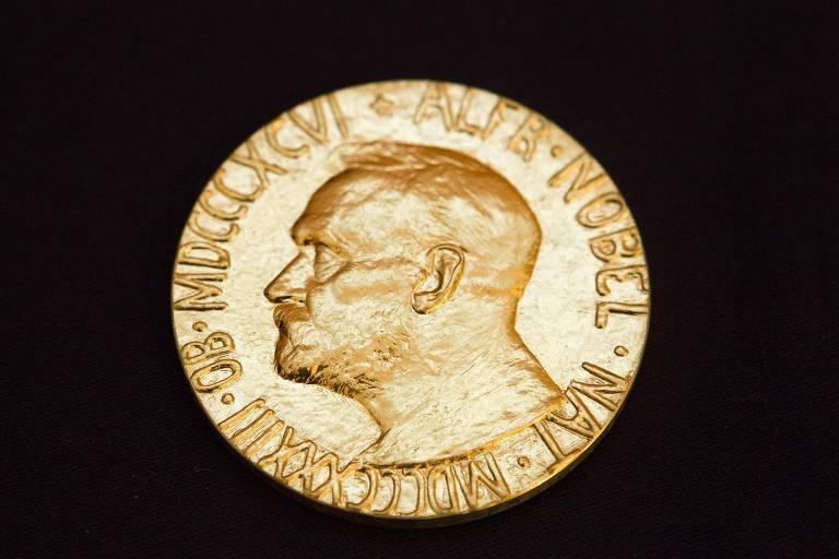 Medalha dourada do Nobel aparece sob fundo preto