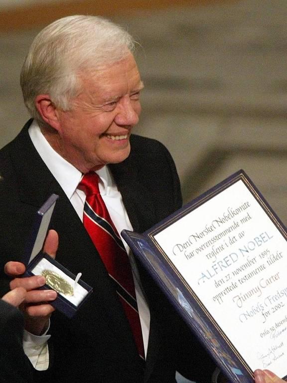 Carter segura a medalha, enquanto outra pessoa que não aparece na imagem está com o diploma do Nobel na mão