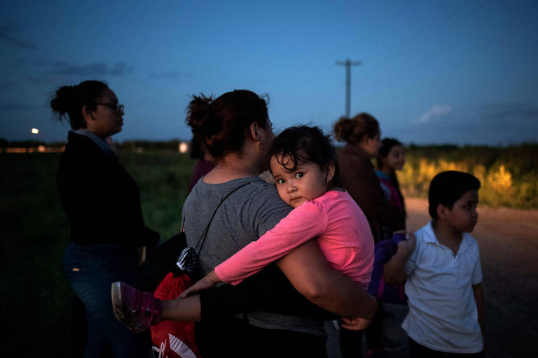Mulher carrega em seu colo uma menina, que usa uma blusa rosa. Ao fundo, outras quatro pessoas e um menino.