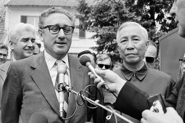 Kissinger (à esquerda) fala ao microfone, ao lado de Le Duc Tho (à direita)