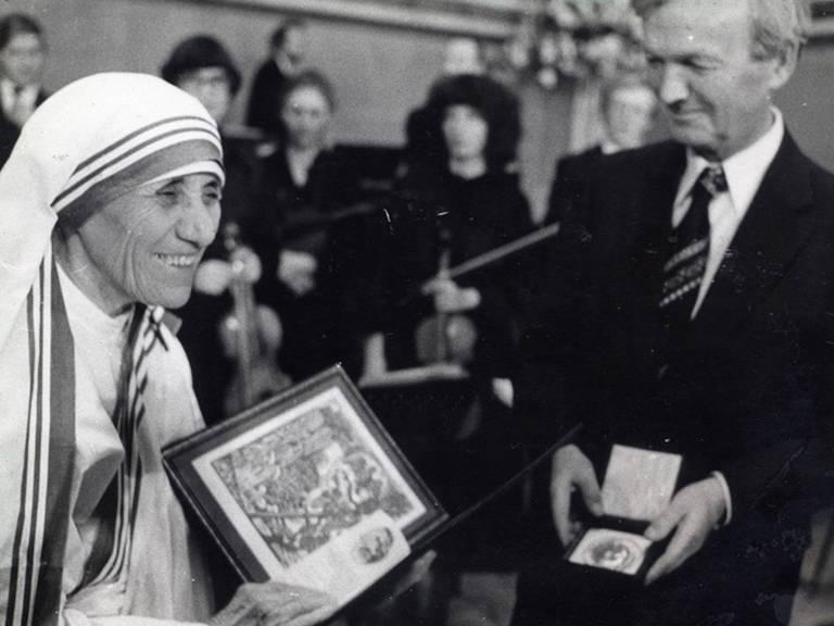 Madre Teresa ri com o diploma do prêmio na mão. Ao lado dela, um membro da comissão do Nobel segura uma medalha.