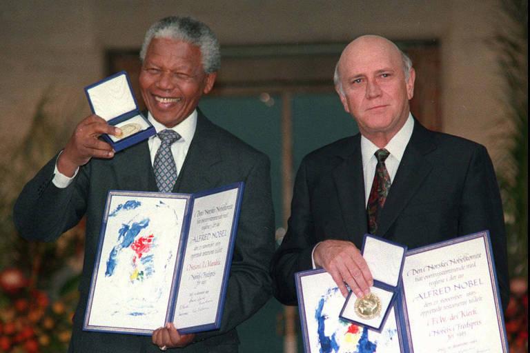 Mandela (à esquerda) sorri e levanta a medalha com uma mão, enquanto segura o diploma com a outra mão. Já De Klerk segura o diploma aberto com uma mão abaixo e outra acima, que também carrega a medalha.