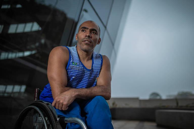 Glebe Candido Alves da Silva em sua cadeira de rodas diante do prédio de treinamento paralímpico em São Paulo