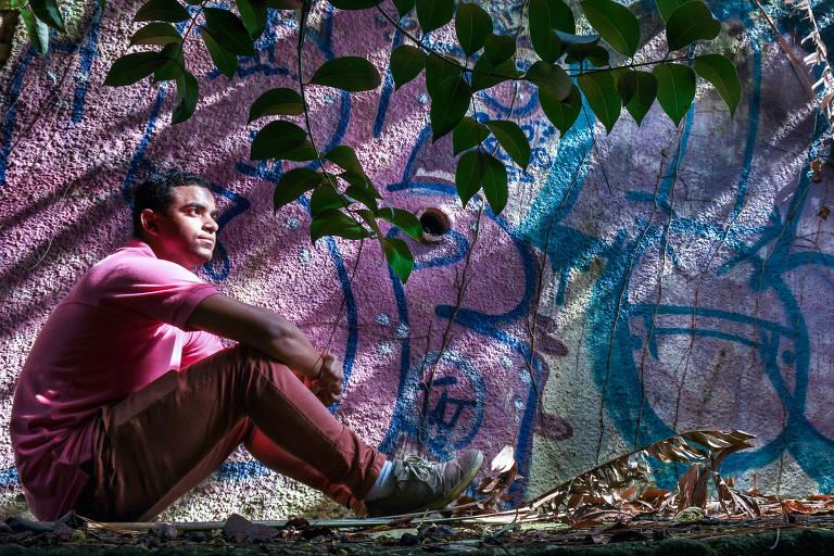 Steve Camilo Gomes de Azevedo, 26, sentado no chão sob as folhas de uma árvore