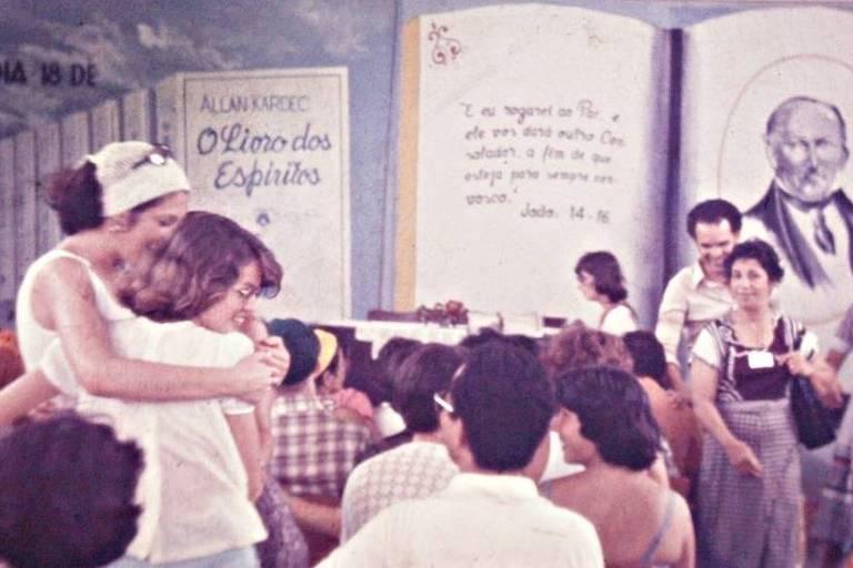 Duas mulheres se abraça, e são observadas por outras pessoas numa reunião