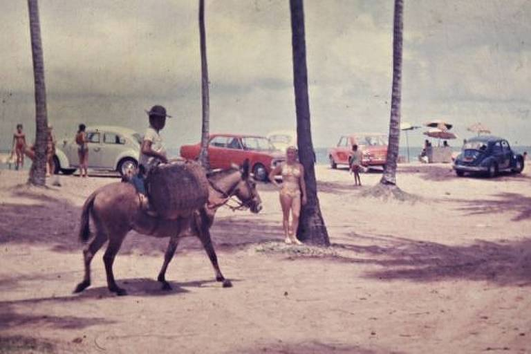 Mulher posa para foto em praia