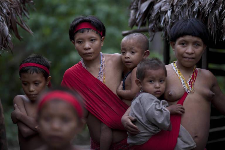 Duas mulheres indígenas seguram bebês com tecidos vermelhos presos aos corpos, ao lado de duas crianças menores, vistas sem foco, diante de duas ocas na flores a meio plano.