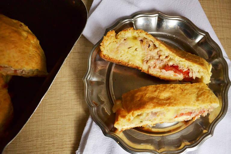Dois pedaços de rocambole assado em travessa; recheio com atum, queijo e tomate está à mostra