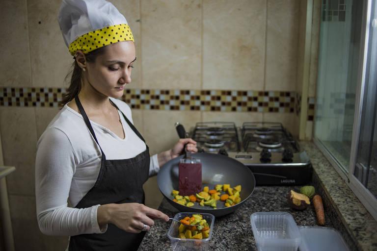 Caroline Domingues prepara marmita em sua casa, na zona leste de São Paulo
