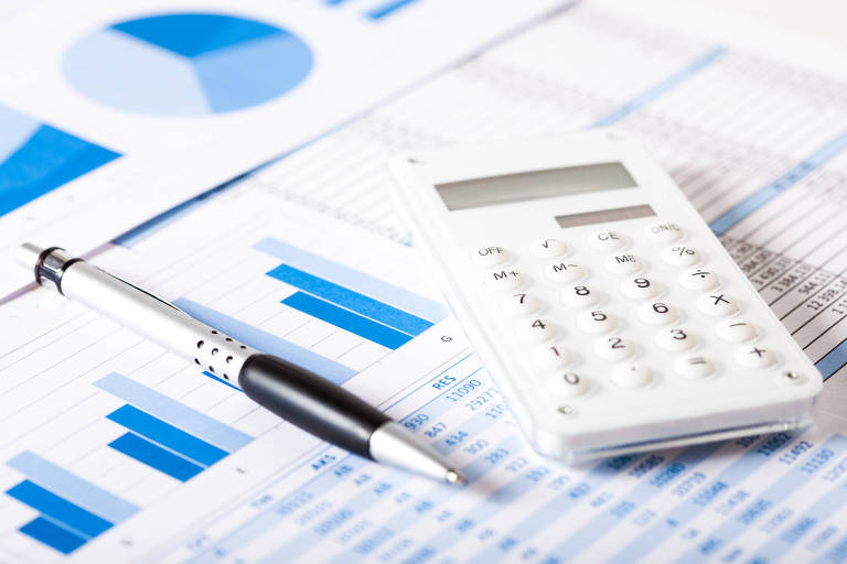 Calculadora, caneta e documentos comerciais