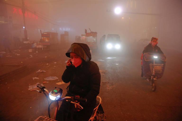 Pessoas na rua em dia de alerta de poluição na China; pessoas em meio a uma espessa névoa