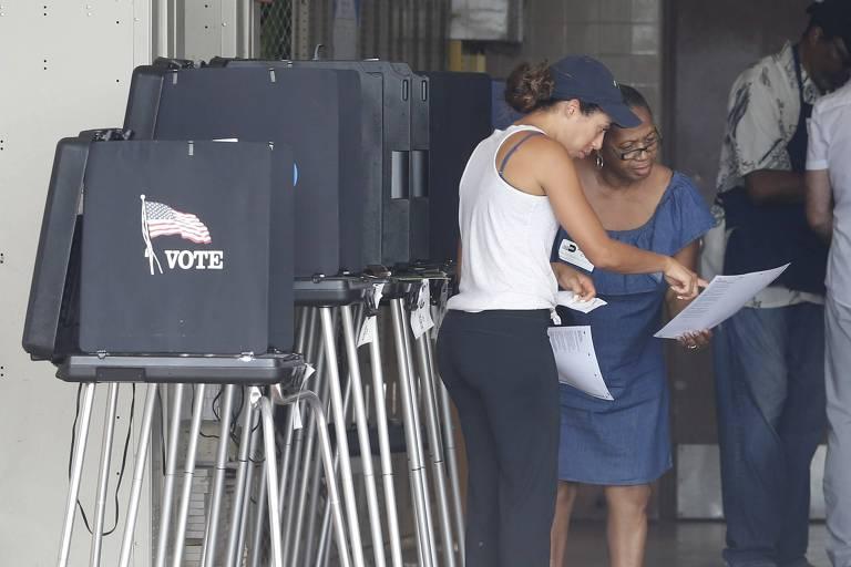 """As duas mulheres estão à direita da imagem, sendo que uma delas carrega um papel na mão para o qual a outra aponta. À esquerda quatro urnas eletrônicas, com um adesivo com a bandeira americana e a palavra """"vote""""."""