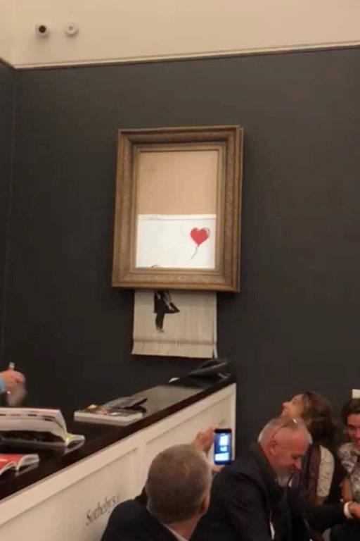 A pintura de Banksy's 'Girl with Red Balloon' na sessão da Sotheby's