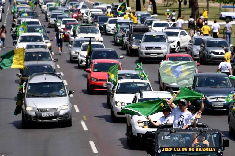 Com bandeiras do Brasil e com a foto de Jair Bolsonaro, apoiadores participam de carreata