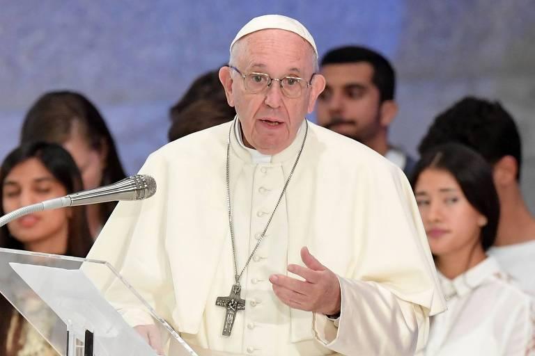 Vestido de branco com uma roupa que cobre até os braços e um grande crucifixo no peito, o papa Francisco faz um discurso