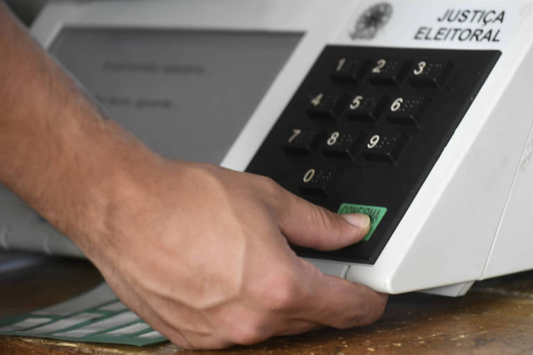 Mão clica a tecla Confirma em urna eletrônica