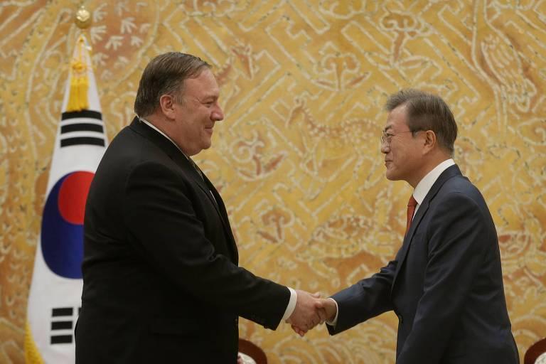 Dois homens de preto aparecem de perfil apertando as mãos, com a bandeira da Coreia do Sul à esquerda, atrás; à esquerda, Mile Pompeo, à direta, o presidente de Coreia do Sul