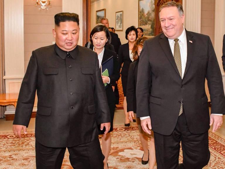 Vestidos de preto, Kim Jong-un  e Mike Pompeo caminham lado a lado