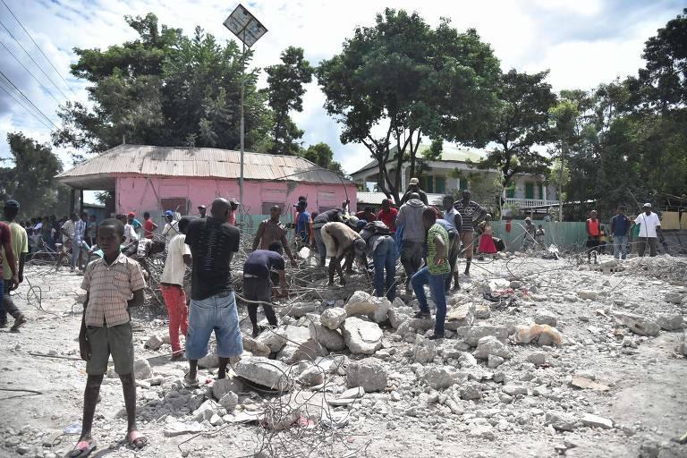 Pessoas ao redor de escombros e poeira do prédio de um auditório que desabou depois de um terremoto no Haiti