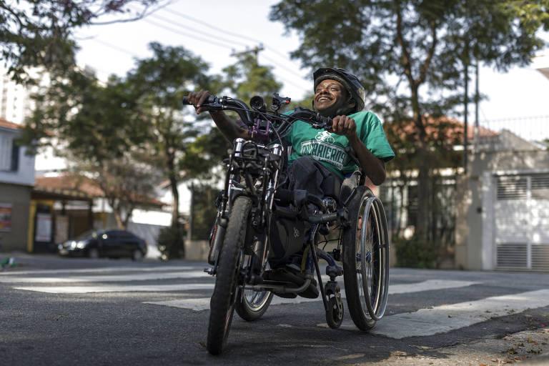 Leonardo Roberto de Souza Lins, 37, posa em uma cadeira de rodas adaptada como bicicleta