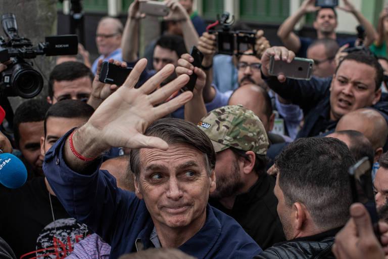 O candidato à presidência pelo PSL, Jair Bolsonaro, acena para apoiadores após votar em um colégio militar no Rio de Janeiro