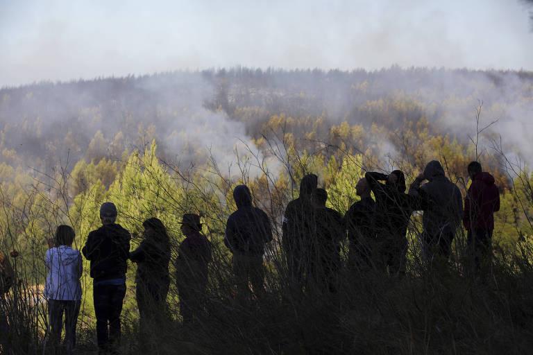 Pessoas olham para floresta em chamas, em Portugal