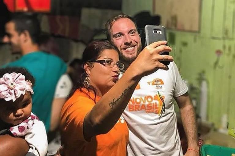 Vestido com camiseta branca com seu nome e número de candidato, Poit posa para selfie tirada por moça de camiseta laranja