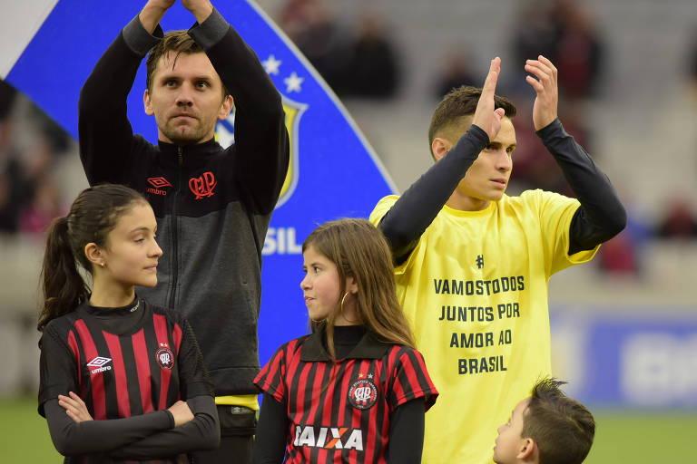 Jogador do Atlético-PR usa camiseta com slogan de Bolsonaro antes de partida contra o América. O zagueiro Paulo André entra em campo com casaco do clube