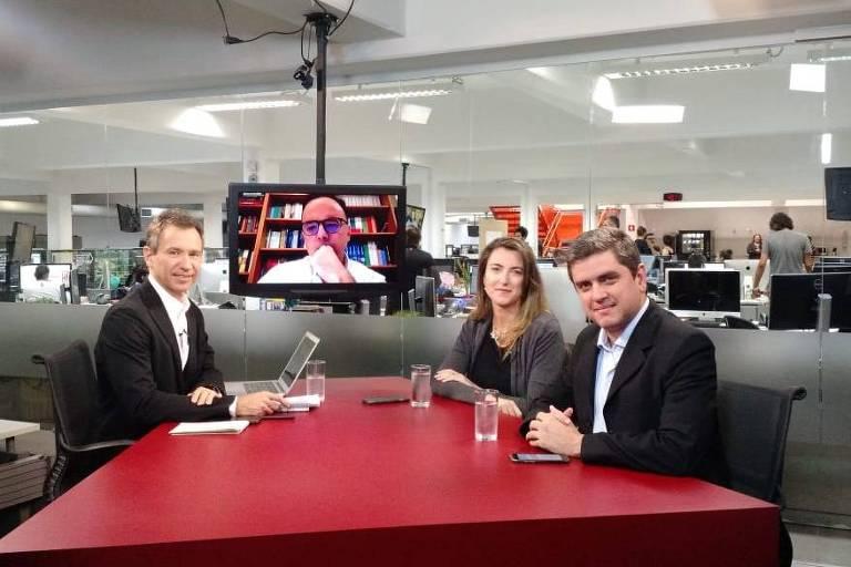 Sentados na mesa do estúdio da TV Folha, os repórteres especiais Fernando Canzian e Patrícia Campos Mello e o editor de Poder, Fábio Zanini, durante debate na TV Folha. Na tela, o colunista João Pereira Coutinho.