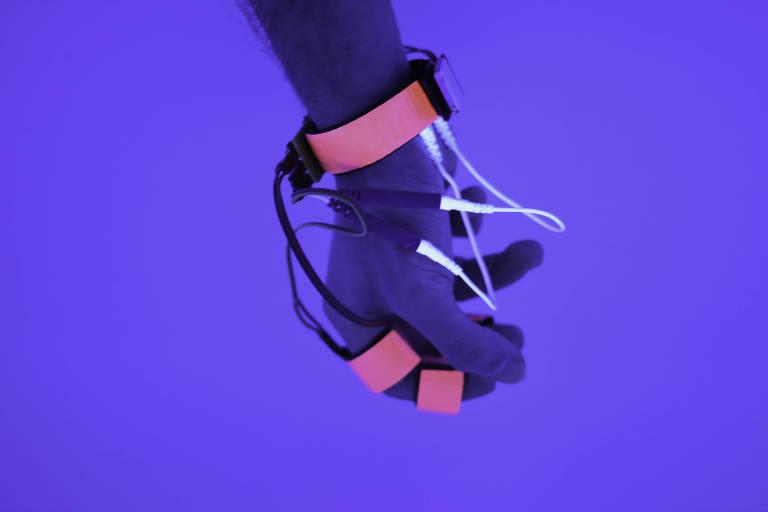 Uma mão é vista com cintas amarradas aos pulsos e ao dedo indicador, de onde saem fios brancos