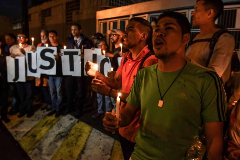 Grupo de 20 pessoas carrega velas e canta gritos de guerra. Parte do grupo carrega letras, que formam a palavra justiça.